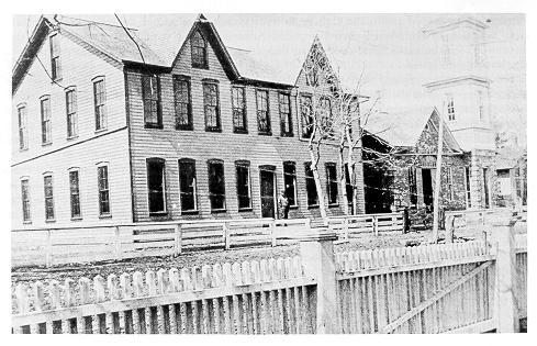 Old black and white photograph of the Mechanical Arts Building (left) and pump houses on unpaved street