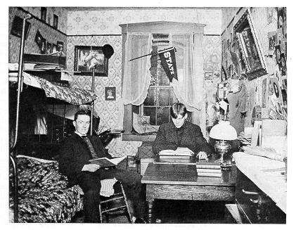 old black and white photograph of students in cluttered dorm room