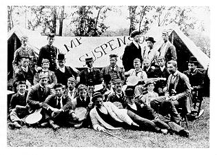 old black and white photograph of students posing at campsite