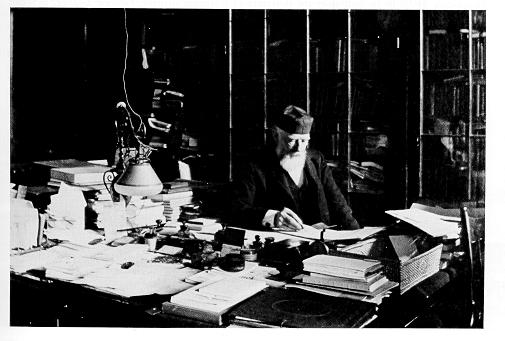 old black and white photograph of George Atherton at his desk in Old Main wearing skullcap hat