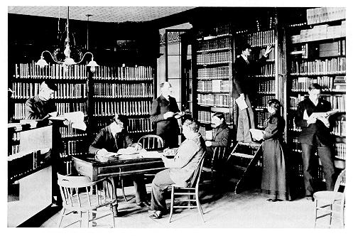 old black and white photograph of Fred Lewis Pattee and students in the library of Old Main.