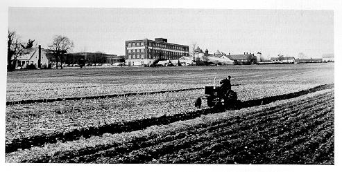 old black and white photograph of a tractor in field