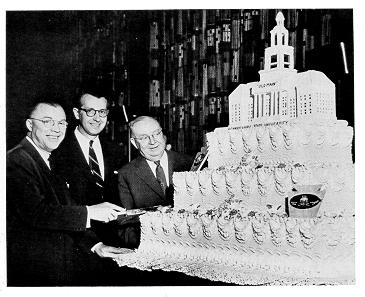 old black and white photograph of Milton Eisenhower, Governor George Leader, and James Milholland posed with the Penn State birthday cake
