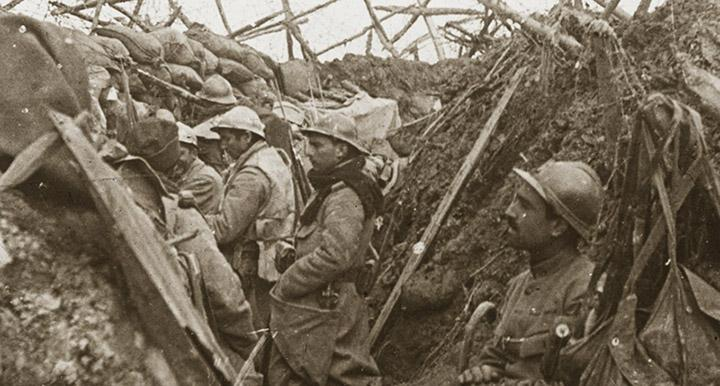 image of World War I soldiers in uniform standing in a field trench on the battlefield